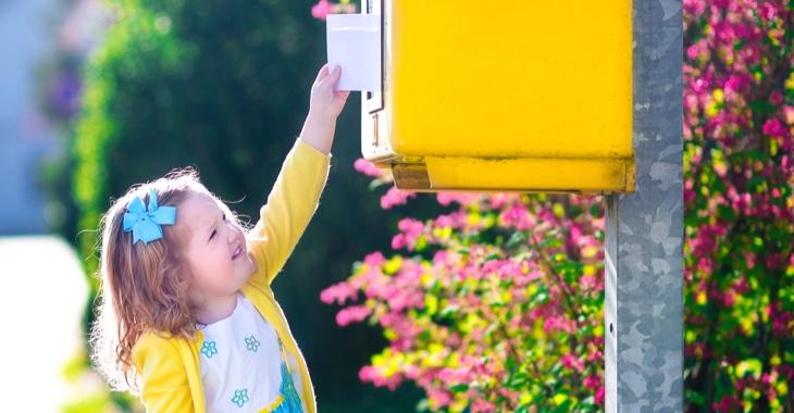Ein kleines Mädchen steckt mit ausgestrecktem Arm einen Brief in einen Briefkasten © iStock/FamVeld