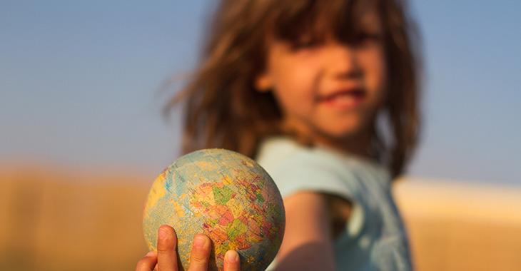 Ein Mädchen hält einen kleinen Globus in der Hand