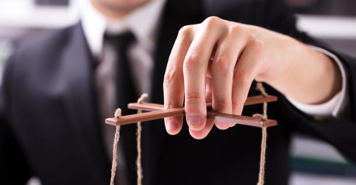 Ein Mann im Anzug und mit Krawatte hält die Fäden einer Marionette @ iStock/AndreyPopov