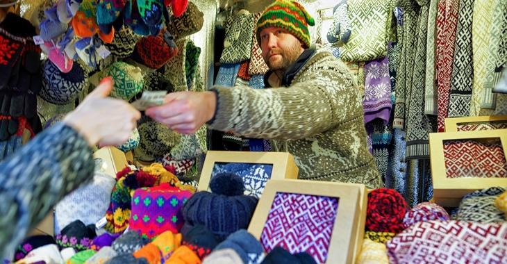 Marktverkäufer mit Strickwaren reicht einer Frau einen Euro-Schein © iStockphoto.com/Roman Babakin