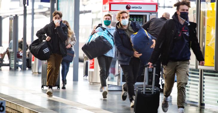 Vier junge Menschen mit Masken und Gepäck auf einem Bahnsteig im Hauptbahnhof Frankfurt am Main © iStock/ollo