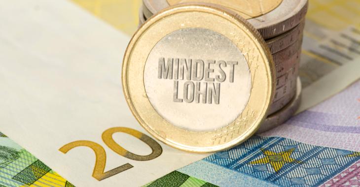 An einen Stapel Euro-Münzen ist eine gangelehnt mit der Aufschrift Mindestlohn © iStock/Stadtratte