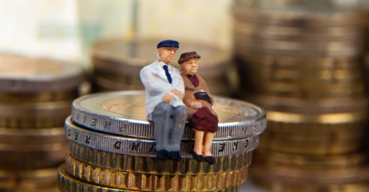 Ein Rentnerehepaar als Miniaturfiguren auf einem Haufen Euro-Münzen © iStock/macgyverhh