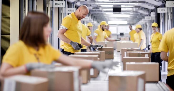 Arbeiter:innen in einem Logistikunternehmen verpacken an einem Fließband Pakete @ iStock/simonkr