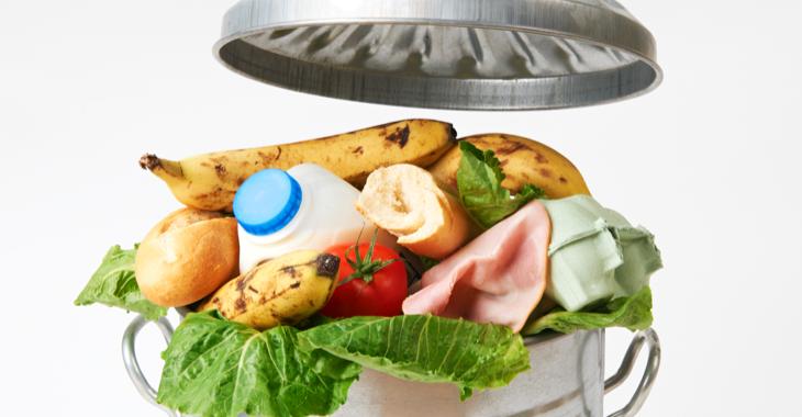 Lebensmittel und Verpackungen in einer Mülltonne mit abgenommenem Deckel © iStock/MachineHeadz