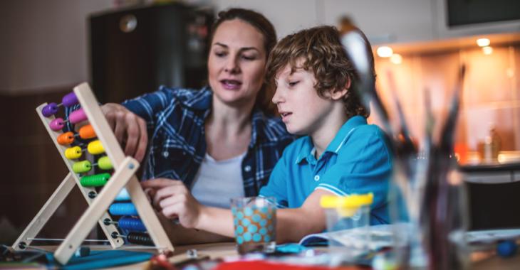 Eine Mutter mit ihrem Sohn rechnen in einem Küche an einem Abakus © iStock/MilosStankovic