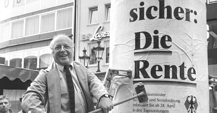 Norbert Blüm am 21. April 1986 mit einem Besen an einer Litfaßsäule mit dem Plakat »Denn eins ist sicher: Die Rente« © picture alliance/Peter Popp