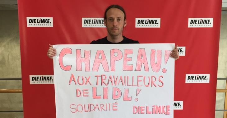 Pascal Maiser hält ein Transparent mit der Aufschrift: Chapeau aux travailleurs de Lidl!