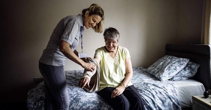 Eine Pflegerin hilft einer älteren Frau beim Anziehen ©iStockphoto.com/SolStock
