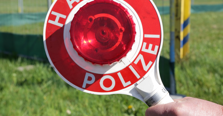 Ein Polizist hält eine Kelle mit der Aufschrift: Halt Polizei © iStock/DinaSigtrix