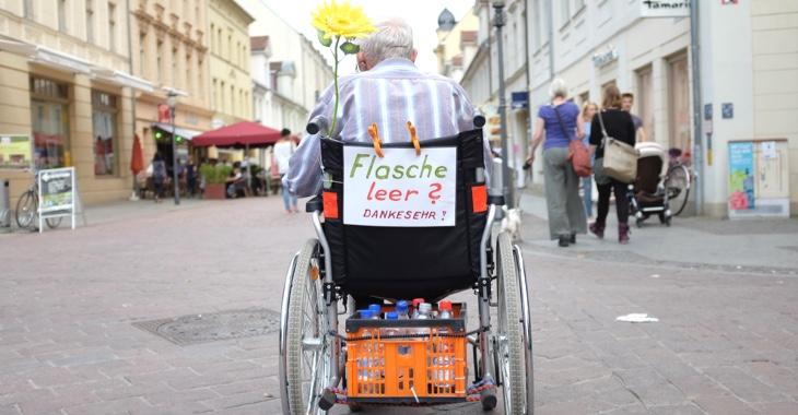 Ein alter Mann im Rollstuhl mit einem Zettel »Flasche leer? Danke sehr!« sammelt in einer Fußgängerzone leere Flaschen © dpa/Kay Nietfeld