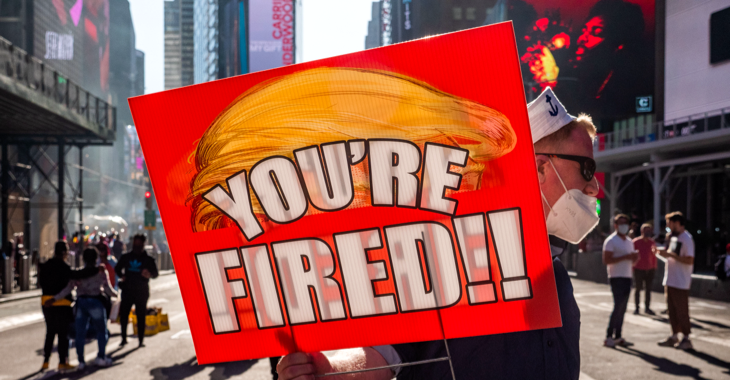 Ein Mann auf dem Times Square in New York hält ein Schild mit stilisierter oranger Trump-Frisur und der Aufschrift: You're fiert! © picture alliance/ZUMAPRESS.com/Milo Hess