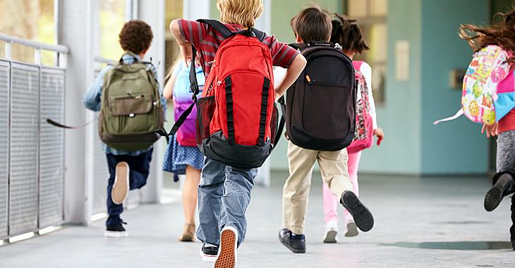 Schulkinder mit Rucksäcken rennen © iStockphoto.com/monkeybusinessimages