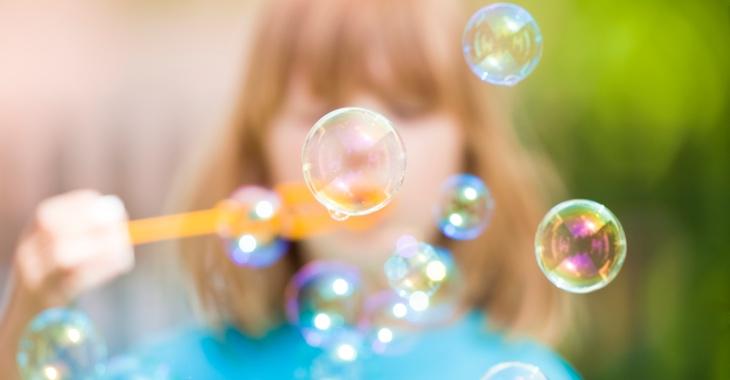 Ein Mädchen pustet Seifenblasen © iStock/courtyardpix