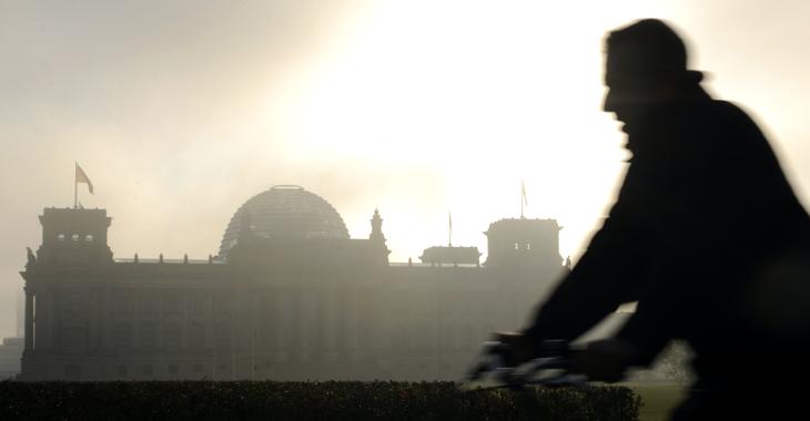 Silhouette eines Fahrradfahrers vor dem Reichstagsgebäude in Morgendunst mit dahinter aufgehender Sonne © picture-alliance/dpa/Rainer Jensen