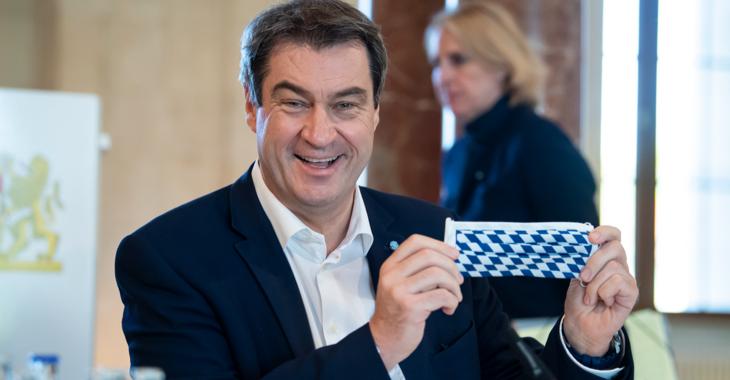 Markus Söder, bayerischer Ministerpräsident und CSU-Chef, hält lachend eine Stoffmaske mit Bayernflagge-Muster © dpa/Sven Hoppe