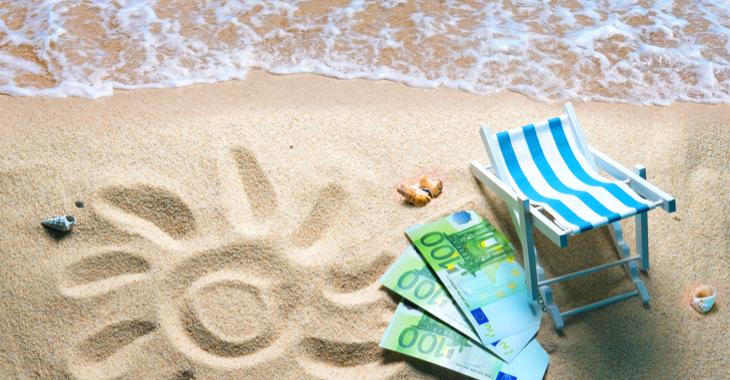 Strand mit Wasser, einer Sonne in den Sand gezeichnet und drei 100-Euro-Scheinen neben einem Liegestuhl © iStock/AlexRaths