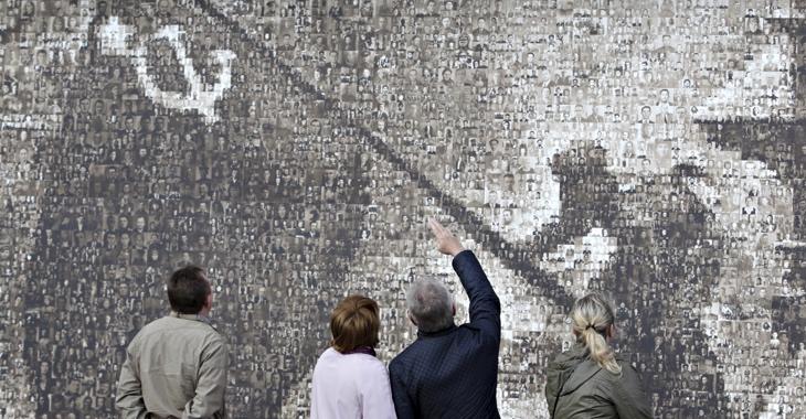 Betrachter vor einer Nachbildung des berühmten Motivs der Sowjetfahne über dem Reichstag, die aus 4.222 Porträtfotos von Einwohnern der russischen Stadt Stawropol, die im Zweiten Weltkrieg ihr Mutterland verteidigt haben, zusammengesetzt ist © REUTERS/Eduard Korniyenko