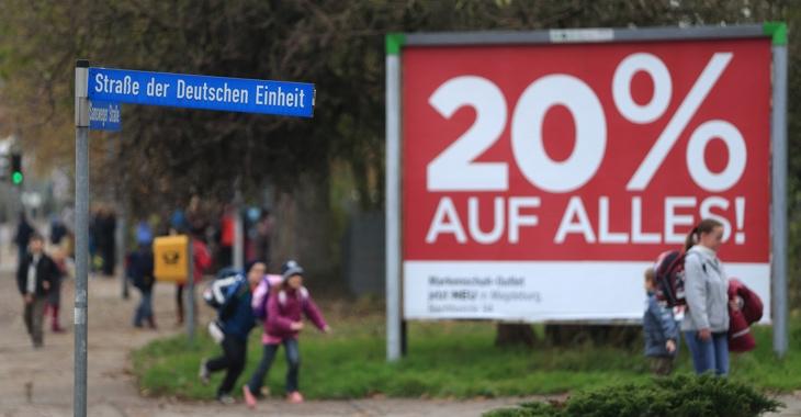Passanten laufen in Wolmirstedt (Sachsen-Anhalt) an einem Straßenschild mit der Aufschrift »Straße der deutschen Einheit« vorbei © dpa