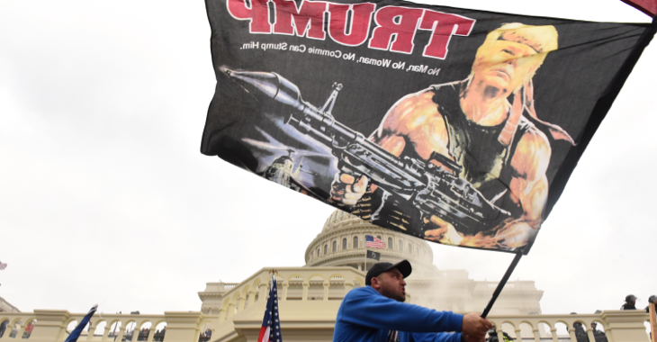 Beim Sturm auf das Kapitol am 7. Januar 2021 in Washington trägt ein Trump-Anhänger eine Fahne, die Trump als Rambo mit Panzerfaust zeigt © REUTERS/Stephanie Keith