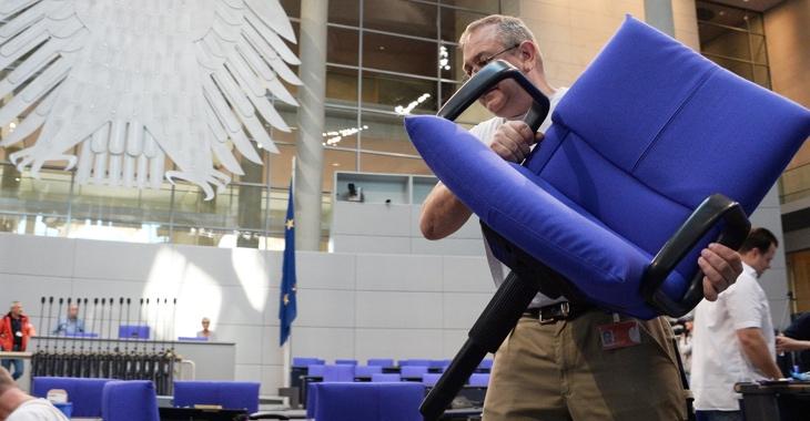 Ein Arbeiter trägt beim Umbau des Plenarsaales des Bundestages einen blau gepolsterten Stuhl © DBT/Achim Melde