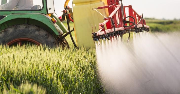 Ein Traktor versprüht Unkrautvernichtungsmittel auf einem Getreidefeld © iStockphoto.com/fotokostic