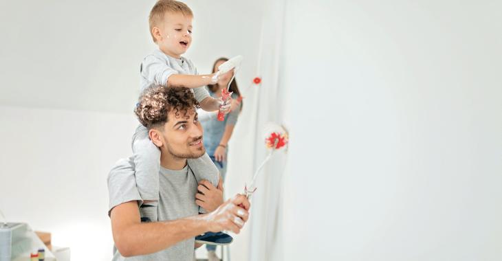 Eine Junge Familie beim Malern ihrer Wohnung, der Sohn mit Farbrolle auf den Schultern des Vaters © iStock/aywan88
