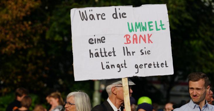 Ein Demonstrationsteilnehmer trägt ein Schild mit der Aufschrift: Wäre die Umwelt eine Bank, hättet ihr sie längst gerettet.
