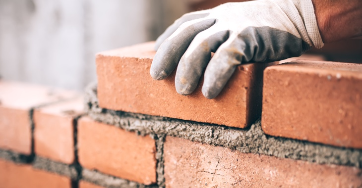 Eine Hand mit Handschuh hält einen Ziegelstein auf einer unvollständigen Wand mit frischem Mörtel © iStock/Bogdanhoda