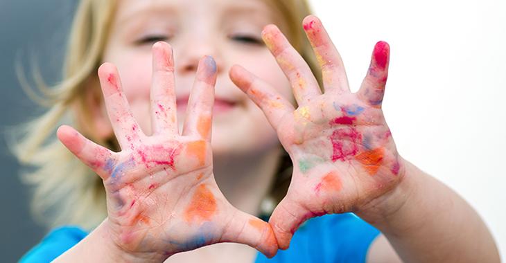 Ein Kind hält zehn mit Farbe bekleckste Finger seiner beiden Hände hoch | Foto: istockphoto.com/Elecstasy