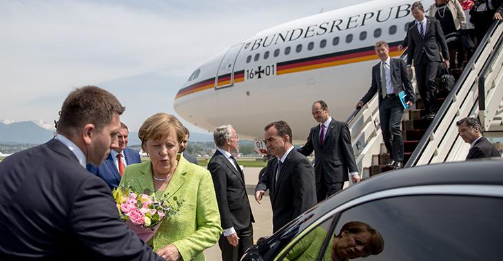 Angela Merkel vor einer Maschine der Flugbereitschaft der Bundeswehr in Sotschi; es steigen weitere Menschen aus der Maschine. | © dpa picture alliance / Michael Kappeler