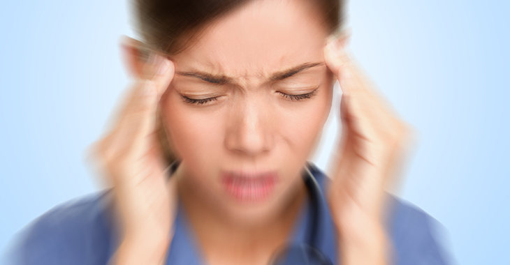 Frau in blauem Hemd fasst sich mit den Fingern beider Hände an die Schläfen und zieht mit geschlossenen Augen die Augenbrauen zusammen. | © iStockphoto.com/Maridav