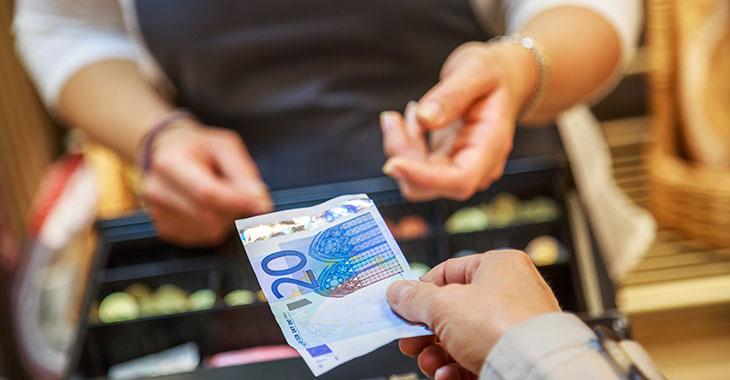 Einzelhandel: Geld wechselt den Besitzer an der Kasse in einem Supermarkt
