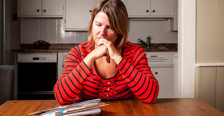 Rechnungen ohne Ende: Besorgte Frau an einem Küchentisch