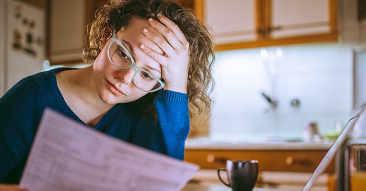 Junge Frau am Küchentisch schaut bestürzt auf Schreiben vom Finanzamt