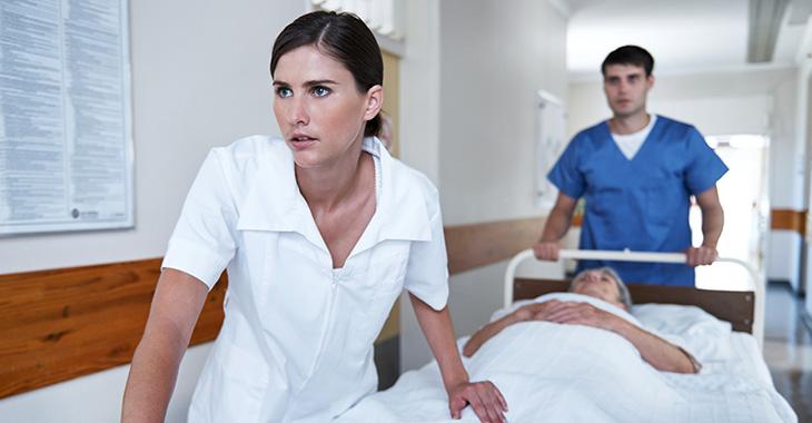 Im Stress: Junge Ärztin und ein Pfleger mit einer Kranken