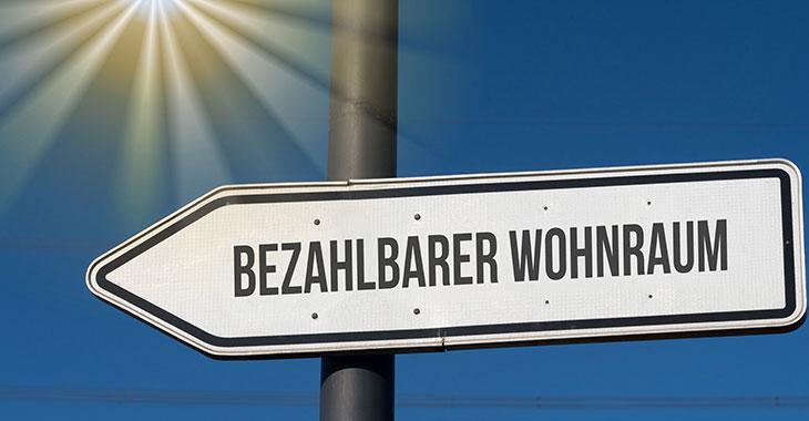 """Schild mit der Aufschrift """"Bezahlbarer Wohnraum"""" vor blauem Himmel"""