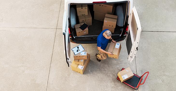 Pakete werden bei einer Lieferung von einem Kurierzusteller in ein Auto geladen. | Foto: © istock.com/Ridofranz