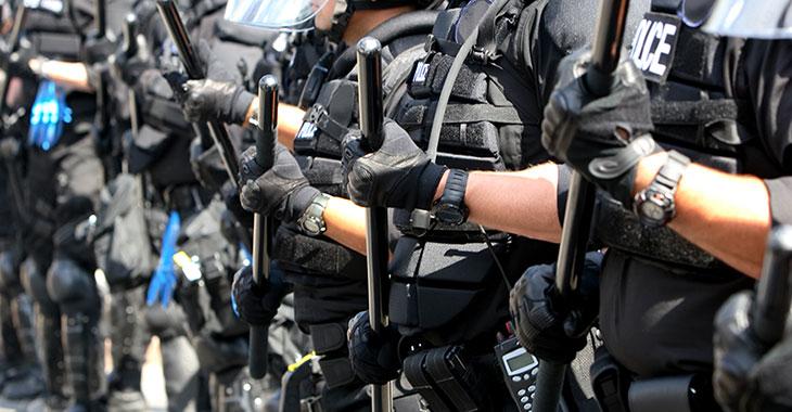 Mehrere Polizisten mit Schlagstöcken