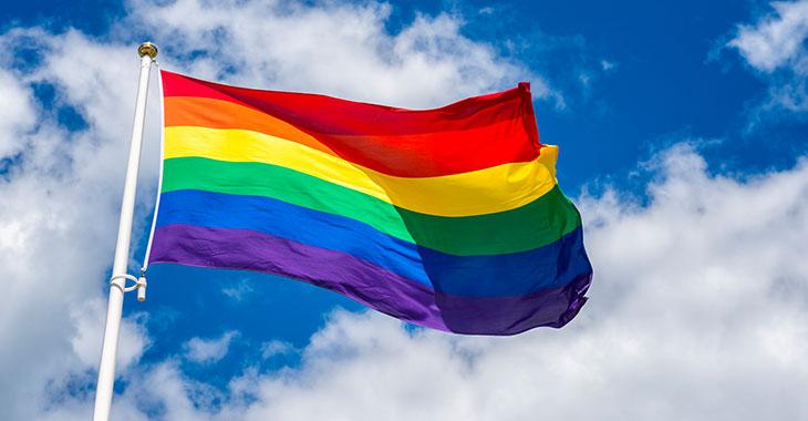Regenbogenfahne vor blauem Himmel