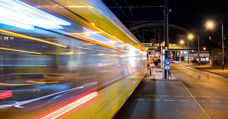 Eine gelbe Straßenbahn fährt nachts in eine Haltestelle ein, die von Straßenlaternen erleuchtet wird. Im Hintergrund ist eine Bahnbrücke zu sehen. Foto: © istock.com/holgs