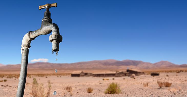 Wasser tropft aus einem Wasserhahn in der Wüste. © istock.com/Angelo D'Amico