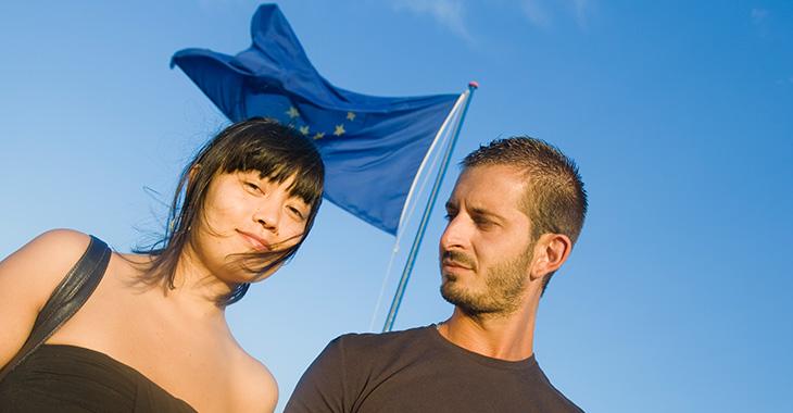 Zwei junge Menschen vor eine Fahne der EU