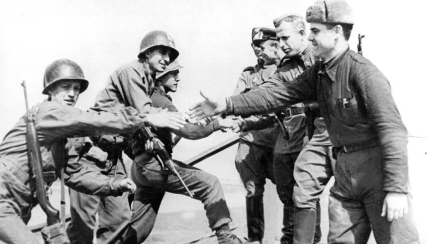 Sowjetische und US-amerikanische Soldaten reichen sich im April 1945 auf den Trümmern einer Elbbrücke bei Torgau die Hände @ dpa