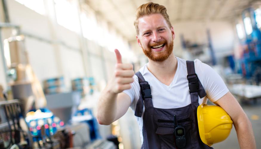 Ein Arbeiter mit gelbem Helm unter seinem linken Arm hebt zustimmend den rechten Daumen © iStock/milanvirijevic