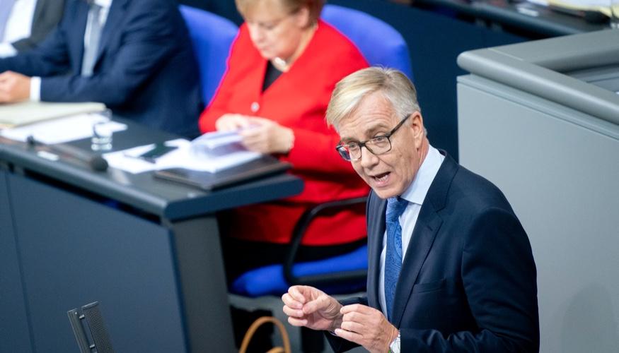 Dietmar Bartsch am Rednerpult des Bundestags, dahinter Kanzlerin Merkel auf der Regierungsbank ©dpa/Kay Nietfeld