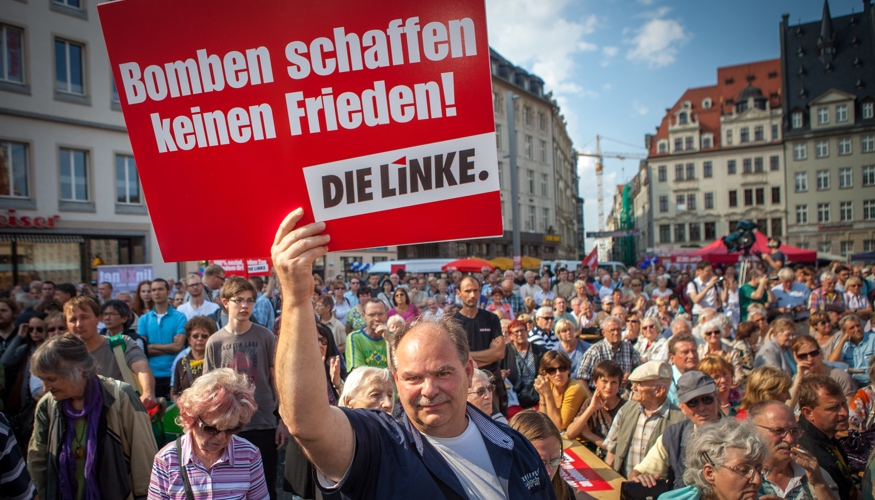 Bei einer Kundgebung in Leipzi hält ein Mann ein Schild mit der Aufschrift »Bomben schaffen keinen Frieden! DIE LINKE« © Jakob Huber