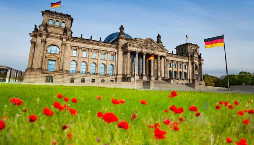 Roter Klatschmohn auf der Wiese vor dem Plenargebäude des Bundestages in Berlin © iStock/SerrNovik