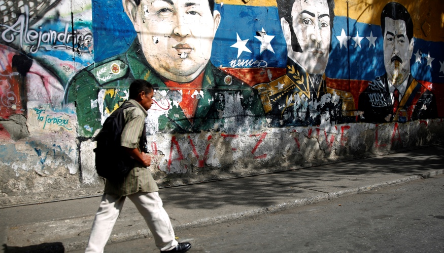 Ein Mann läuft am 30. Januar 2019 in Caracas, der Hauptstadt von Venezuela, an einem Graffiti vorbei, das die Köpfe von Hugo Chavez, Simon Bolivar und Nicolas Maduro zeigt © REUTERS/Carlos Barria