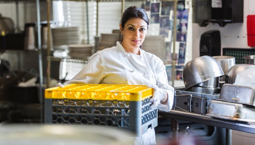 Eine Arbeiterin mit Abwaschpaletten in einer gewerblichen Großküche © iStock/kali9